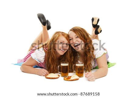 two laughing bavarian girls with beer and pretzels on the floor on white background - stock photo