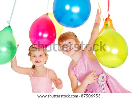 Two laughing kids playing with colorful balloons - stock photo
