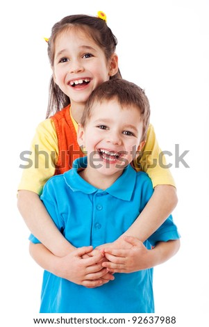 Two laughing little children standing together, isolated on white