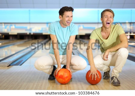 Two laughing men sit on floor with orange balls in bowling club; shallow depth of field; full body - stock photo