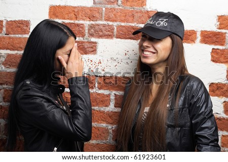 Two laughing women red bricks wall background. More images of this models you can find in my portfolio - stock photo