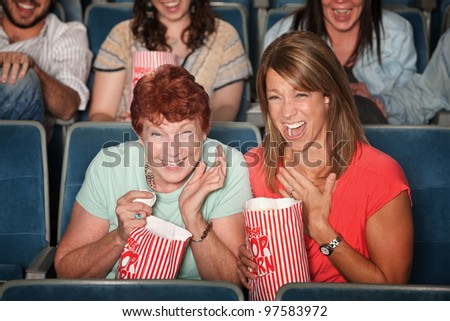 Two laughing women with popcorn bags at a picture show - stock photo