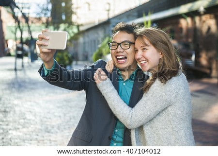Two laughing young people taking a selfie with mobile device outside on city street - stock photo