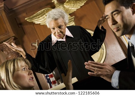 Two lawyers arguing with judge standing above them in courtroom - stock photo
