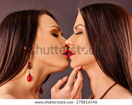 Two lesbian women with closed eyes kissing .Grey background. - stock photo
