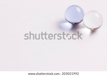 Two light blue and clear glass marbles - Upper right  - stock photo