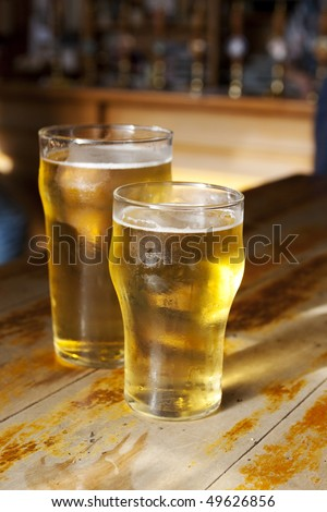Two light golden beers on a wooden bar - stock photo