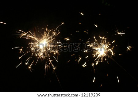 Two light sparklers at dark background