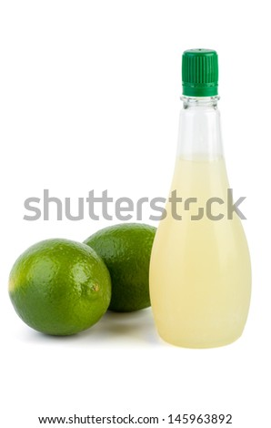 Two limes and bottle of juice isolated on the white background - stock photo
