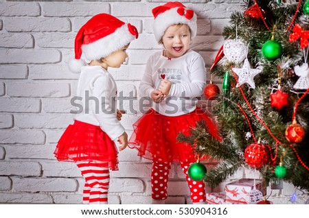 Two little adorable girls in red santa's suit standing near christmas tree and having fun. Children happy. New year photo.