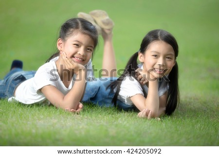 Two little asian girls laying on the green grass - stock photo