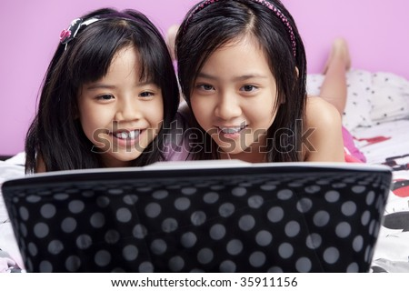 Two little Asian girls playing with laptop in the bedroom - stock photo