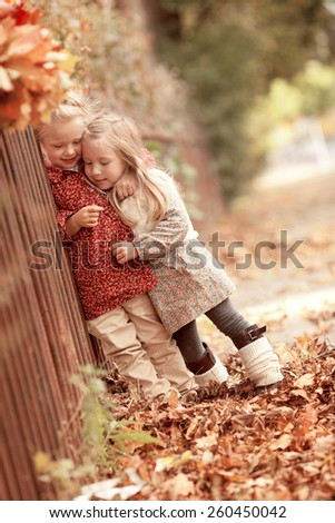 two little beautiful girls friends are standing arm in arm near the fence in the autumn park