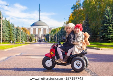 Two Little beautiful sisters sitting on toy motorcycle in big park - stock photo
