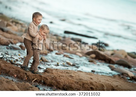 two little blond boys brothers in beige sweaters and brown jeans standing in stony beach with sand near the sea