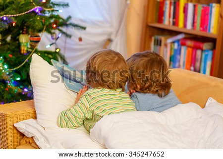 Two little blond children reading a book together in bed near Christmas tree with lights and illumination. Happy family, two friends, kid twins boys. - stock photo