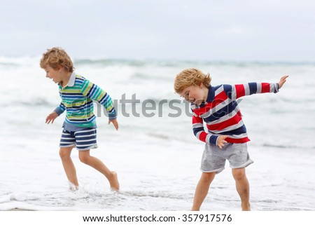 Two little blond kid boys having fun on lonely ocean beach. Children playing and running on stormy windy bad weather day. - stock photo