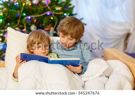 Two little blond sibling boys reading a book together in bed near Christmas tree with lights and illumination. Happy family, two children and friends. - stock photo