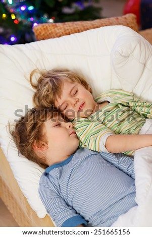 Two little blond twins sleeping in bed near Christmas tree with lights and illumination. Tired kids dreaming and relaxing. Happy family of two brothers. - stock photo