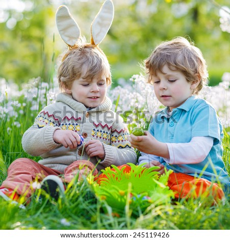 Two little boy friends in Easter bunny ears during traditional egg hunt in spring garden, outdoors. On warm sunny day with blooming trees on background.