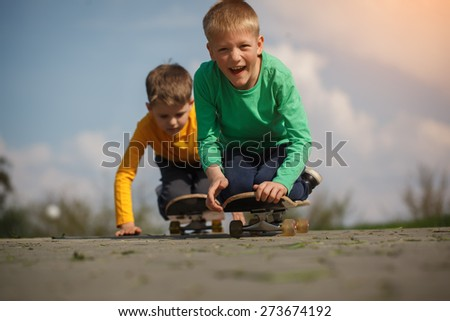 two little boy  skating on the street in summer day
