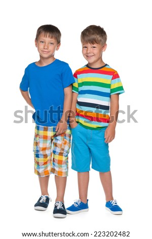 Two little boys are standing together on the white background - stock photo