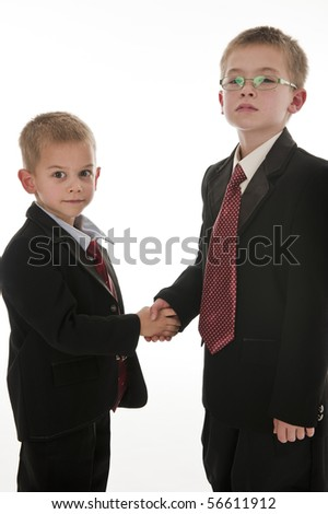 Two little boys dressed up in suits pretending to be businessmen and shaking hands. Isolated on white. - stock photo