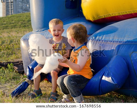 Two little boys eating candy floss laughing with enjoyment as they sit together on a plastic jumping castle at a funfair - stock photo