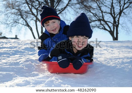 Two little boys have fun together sliding downhill on a pleasant winter day. - stock photo