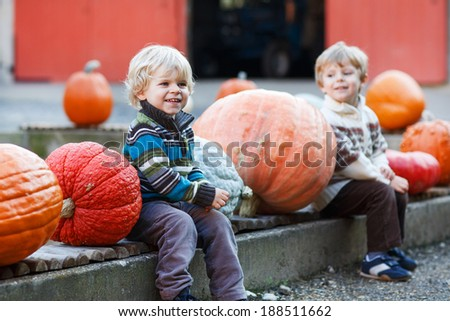 Two little boys having fun with pumpkins on pumpkin patch on farm. Selective focus on one boy. - stock photo
