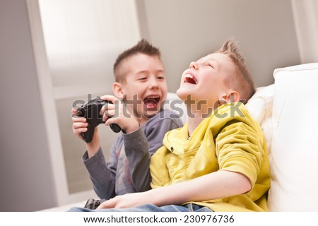 two little boys having lots of fun with video games - stock photo