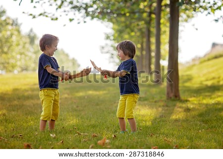 Two little boys, holding swords, glaring with a mad face at each other, fighting outdoors in the park - stock photo