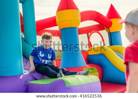 Two little boys in short sleeve shirts playing on inflatable slide and castle outdoors - stock photo