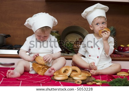 two little boys in the cook costumes at the kitchen sitting on the table
