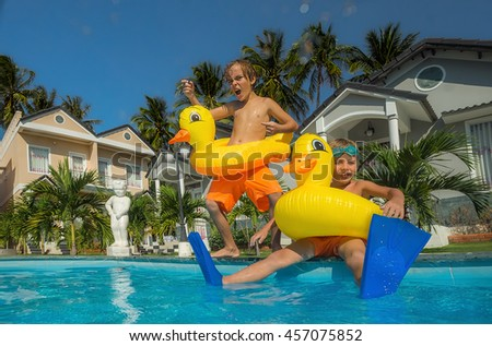 Two little boys in the swimming pool - stock photo