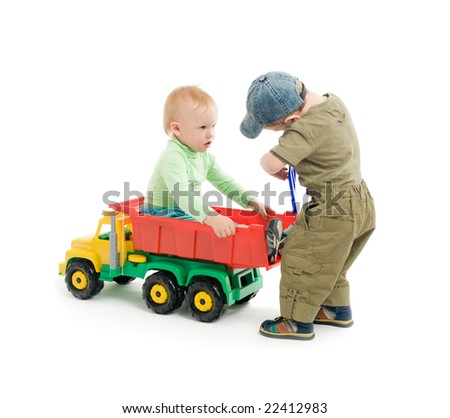 Two little boys play with toy truck. One boy sit on the car and second boy repair the car's body