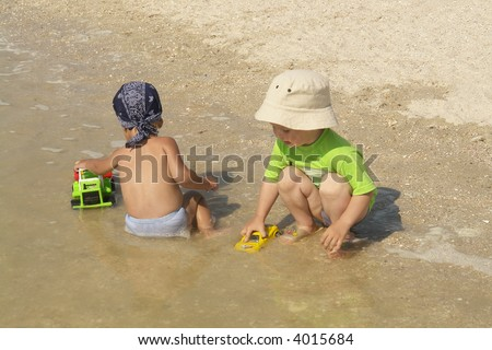 two little boys playing in the water - stock photo