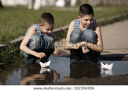 two little boys playing with paper boats in puddle - stock photo