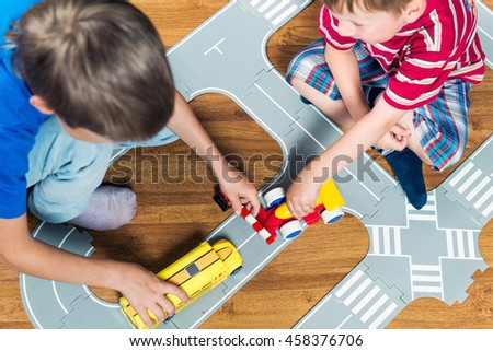 Two little boys plays with toy car