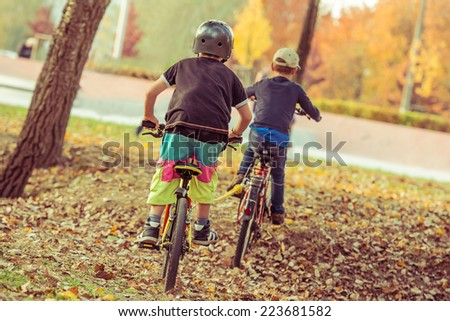Two little boys riding bicycles in the park - stock photo