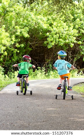 two little boys riding their bikes along a shaded park trail - stock photo