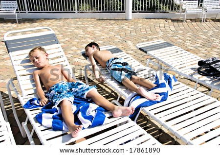 Two little boys sunbathing lying in lounge chairs by a pool. - stock photo