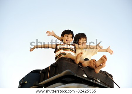 Two little boys traveling on bags, the top of the car - stock photo