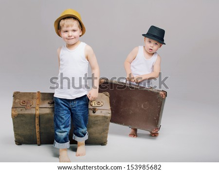 Two little boys walking with suitcases - stock photo