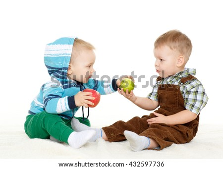 Two little boys with fresh apples sit on a white background. Healthy food. - stock photo
