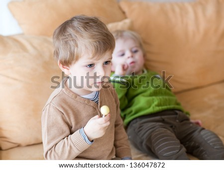 Two little brother boys watching tv and eating candy indoor. Selective focus on child on foreground.