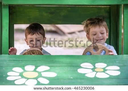 Two little brother toddlers playing with toy car in summer garden. Boys having fun and good time. In wooden toy car at playground.