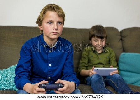 two little brothers on a couch, one with a gamepad the other with his tablet - stock photo