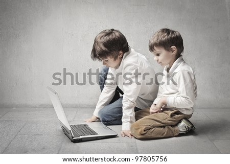 Two little brothers using a laptop - stock photo
