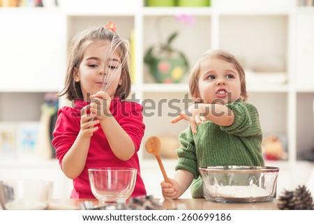 Two little chefs having fun preparing cookies - stock photo
